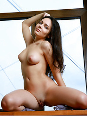 Bridgette Angel strips by the window baring her sexy body with delectable tits.