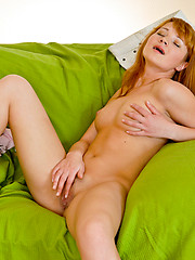 Blonde nubile relaxing on the green sofa