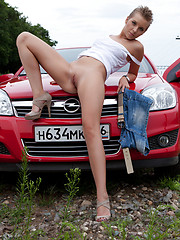 Gorgeous short haired teen beauty stripping and spreading legs outdoor near the red car.