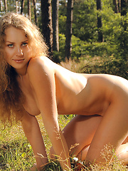 Admirable naked charmer demonstrating her natural femininity and passion in the forest.
