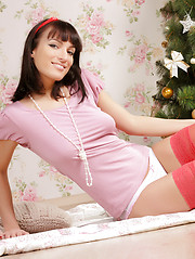 Amazing dark haired girl with impressive tits in red stockings posing near the New Year tree.