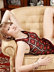Delightful beauty with seductive eyes taking off clothes and spreading legs on the armchair.