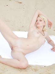 Marvelous blonde hottie posing in the nude with an inflatable ball outdoor on the sand.