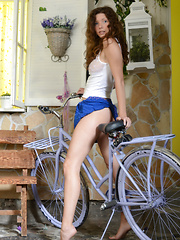 Wonderful slender dark haired lassie stripping and posing in the nude near her bicycle.