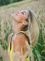 With a confident, charming allure, Taylor is a stunning sight as she strips her hot yellow dress amidst the tall, verdant grass and tree.