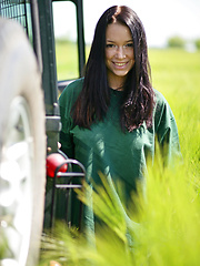 Gwen playfully strips her green shirt matching the green grassy field and poses naughtily all over the jeep, flaunting her awesome physique and gorgeous breasts.