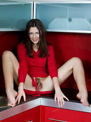 Wearing a bright red dress, Quinn is a sumptuous feast for the senses as she showcases her smooth, fair-skinned body and fresh assets on the kitchen.