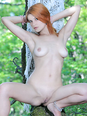 Violla portrays an enchanting forest nymph with her smooth, creamy white skin, round puffy breasts, pink pussy, and pretty, alluring face as she poses seductively amongst the trees.