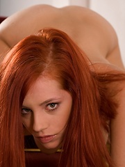 Fiery red Ariel reveals her round breasts and clean bush while straddling stairs.