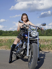 Wearing a sexy leather dress and boots Milena displays her petite and nubile body on top of a motorcycle