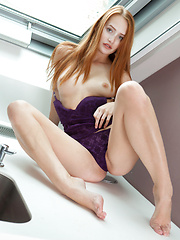 Denisa flaunts her sexy, athletic, long legs and delectable sweet pussy by the kitchen sink.