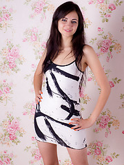 Delectable teen sweetie with groomed dark hair undressing and posing with a painting frame.
