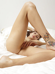 Short-haired skinny model relaxing in the bed