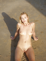 Hot blondie lying on the sand