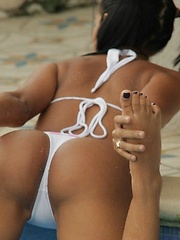 Karla jumps in the pool to cool off in her white and pink bikini