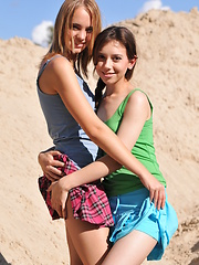 Two perfect lesbian girlfriends demonstrating their alluring bodies outdoor in the sandpit.