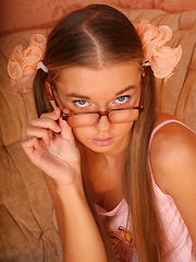 Yummy girl wearing pigtails and glasses playfully strips revealing her nice tits and pussy.