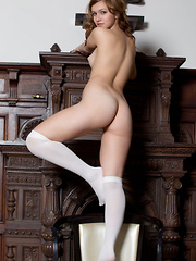 Demetra A is an unshaved beauty, an exqusite site to behold. Adorable in her white knee socks she exposes her lovely feminine bush.