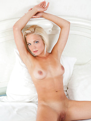 Blonde bombshell with sparkling blue eyes, Nena looks inviting as she's sprawled in bed wearing her matching white lingerie