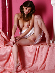 The bubblegum pink background compliments Anita C's sweet and charming allure and her smooth and puffy assets.