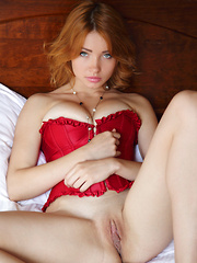 Kika's bright red corset compliments her fair, porcelain smooth skin, highlighting her perfectly round breasts, slim waist, and smooth shaven labia as she sprawls enticingly on top of the bed.
