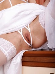 Divina A sensually removes her white long dress, revealing her smooth, athletic body garbed in string lingerie and sheer stockings that amplified her erotic looks.