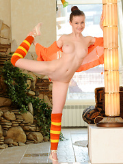 Emily Bloom looks delicately sweet and sexy in orange cardigan, striped legwarmers, and ballerina shoes, showing off her body's flexibility with en pointe poses.