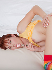 Redhead chick Delila Darling bent over on the couch in her rainbow socks stuffing her tiny pussy with a glass dildo