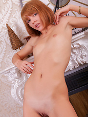 Pretty redhead with youthful appeal, Silviann A spreads her legs wide open on top of the couch.