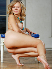 Olivvia A smiles enticingly as she cups her round, puffy breasts before posing confidently before Alex Sironi\'s camera.