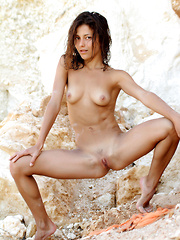 Divina A's slender body, an undeniably pretty face, and sultry allure is a pleasing break from the rugged rocks and desolate terrain on her background.